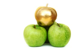 image of one gold apple among regular green ones
